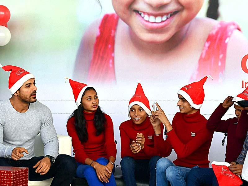John Abraham chats with the kids at a function for the underprivileged children, in New Delhi on Monday. (PTI Photo)