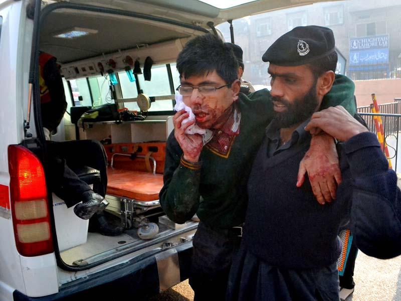 A student injured in the shootout at Army Public School in Pakistan's Peshawar is helped by a hospital security guard. (AP Photo)