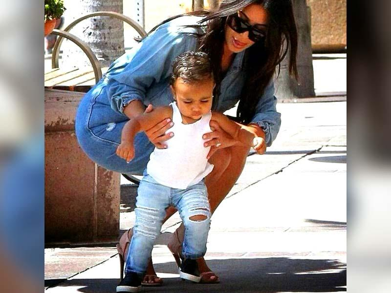 Being the daughter of famous reality TV star Kim Kardashian and rapper/fashion god Kanye West means that North West must look her fashionable best -- always. Nevermind, she's only 17-months-old! If being usually seen in mini versions of mom Kim's designer outfits isn't fashionable, what is? See some of the cutest pictures of North West and be the judge. | Here, baby Nori is taking a walk with her mom while rocking those ripped jeans. Isn't she killing it? (Text: Sanya Panwar)