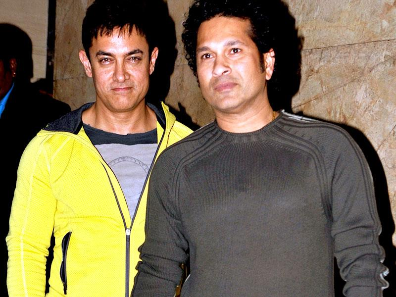 Former Indian cricketer Sachin Tendulkar and Bollywood actor Aamir Khan pose for a photograph at the screening of forthcoming PK in Mumbai on December 16, 2014. (AFP Photo)