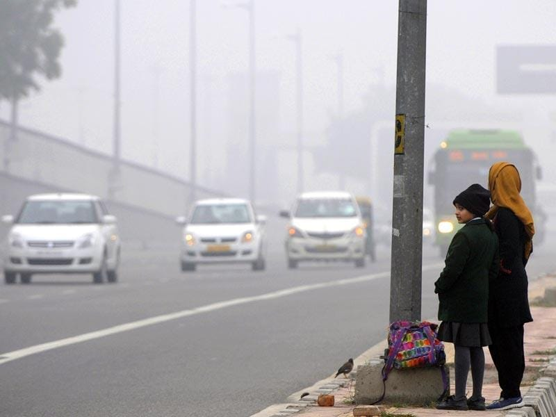 A school student waits during a cold and foggy morning, at Mayur Vihar, in New Delhi. (Sushil Kumar/HT Photo)