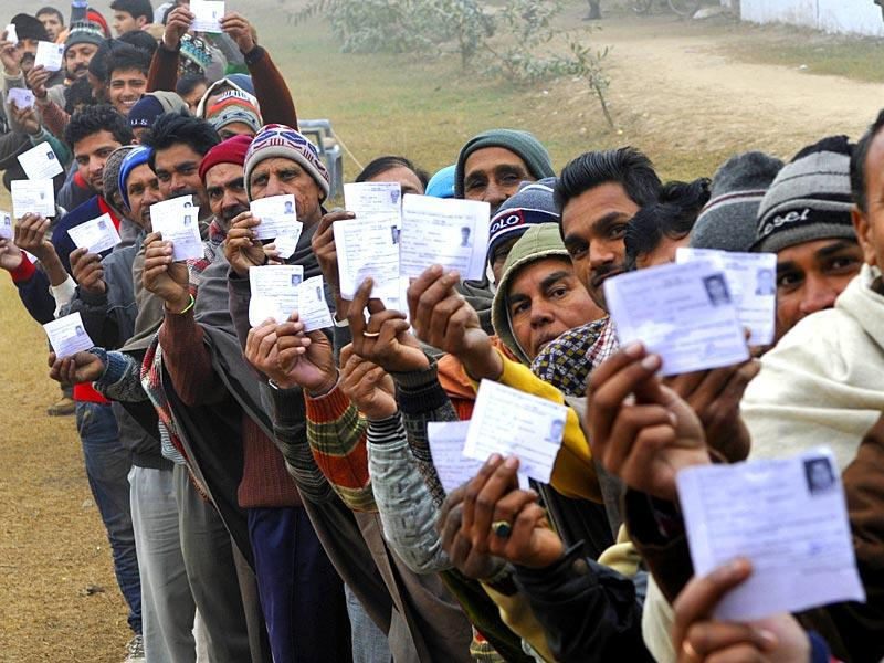 Voters stand in a queue to cast their votes at a polling station during the assembly elections in RS Pura, about 30 km from Jammu. (Nitin Kanotra/HT Photo)
