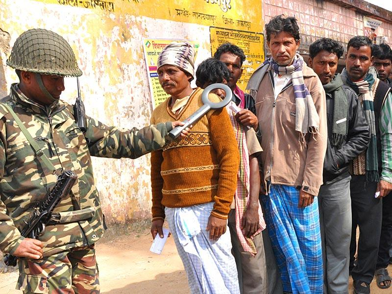 A police personnel checks a voter with a metal detector before letting him inside the polling booth at Dharampur. (Bijay/HT Photo)