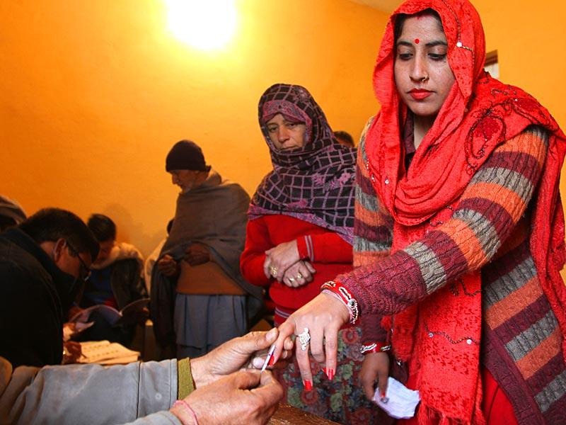 A polling officer marks the finger of a voter with indelible ink inside a polling station during the fifth phase of voting, at Satrayan village near the India-Pakistan international border near Jammu. (AP Photo)