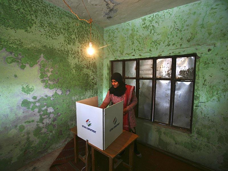 A woman casts her vote at a polling station during the fifth and last phase of the Jammu and Kashmir state assembly elections on the outskirts of Jammu. (Reuters)