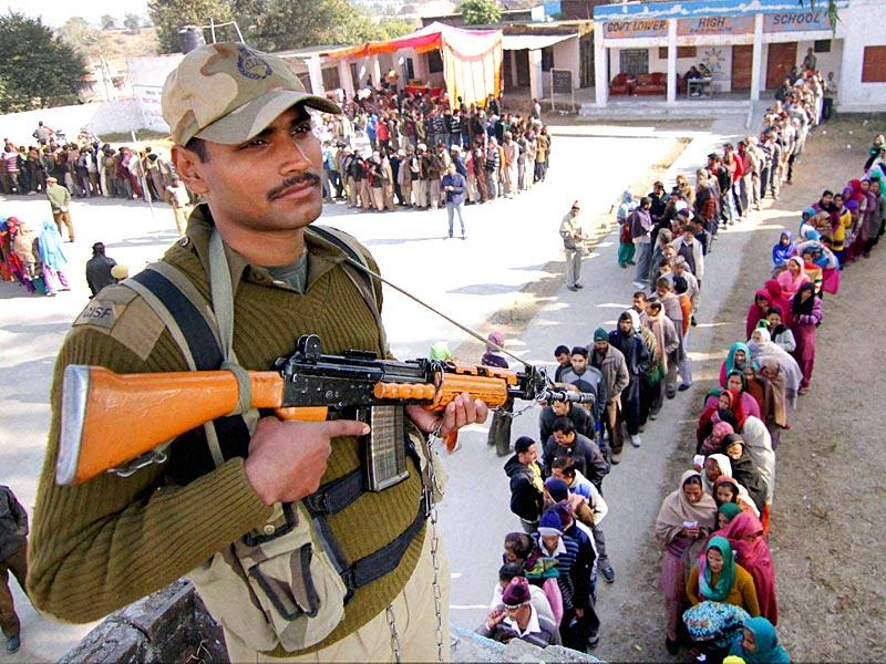 A security person keeps vigil at a polling station during the Jammu and Kashmir assembly elections. (PTI Photo)