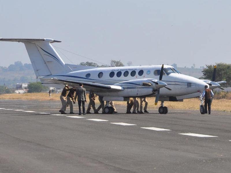 Policemen manually push MP chief minister Shivraj Singh Chouhan's plane off the runway in Chhindwara on Monday. (HT photo)