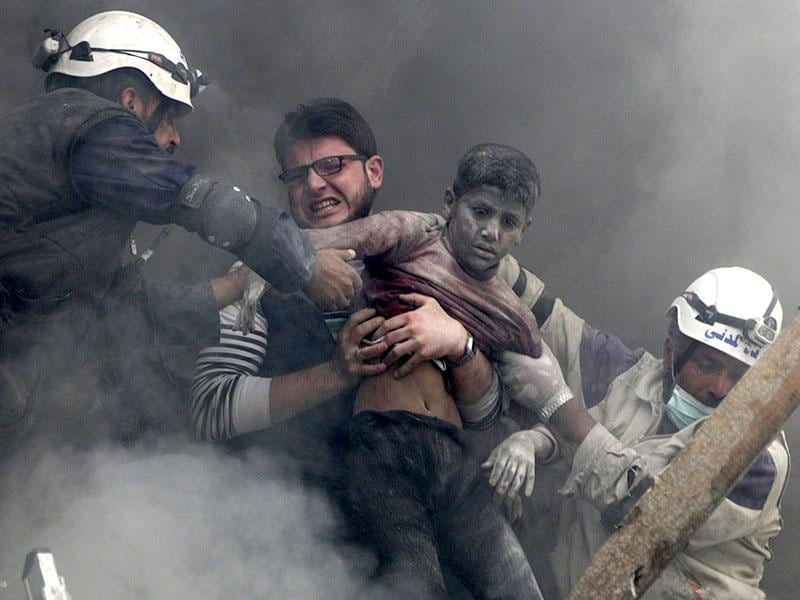 Men rescue a boy from under the rubble after what activists said were explosive barrels were dropped by forces loyal to Syria's President Bashar Al-Assad in the Al-Shaar neighbourhood of Aleppo. (Reuters Photo)