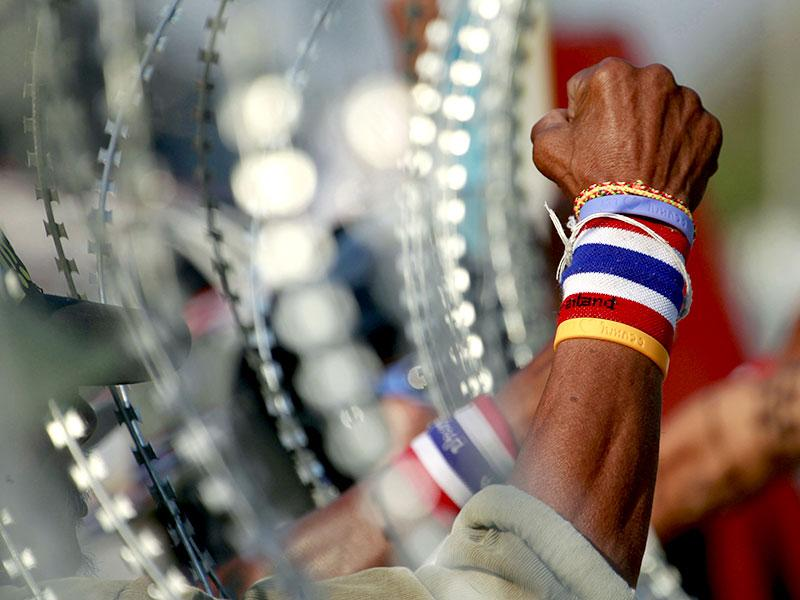 Anti-government protesters chant slogans next to a line of barbed wire during a rally outside the Center for Maintaining Peace and Order (CMPO) on the outskirts of Bangkok, Thailand. (AP Photo)