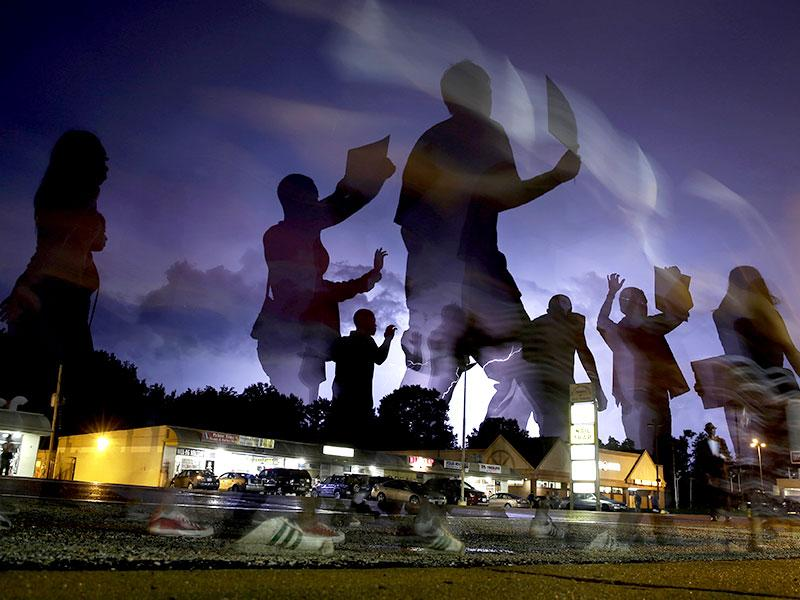 Protesters march in the street as lightning flashes in the distance in Ferguson. (AP Photo)