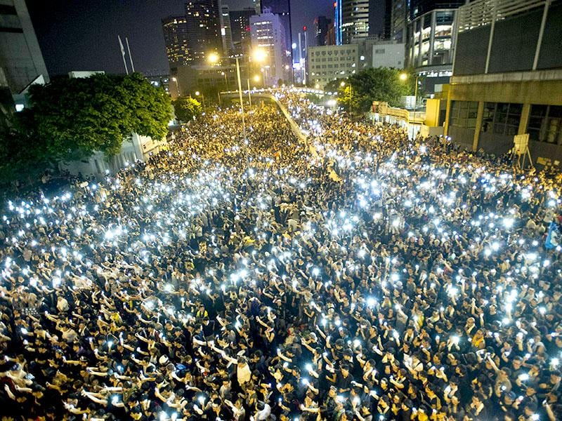 Protestors and student demonstrators hold up their cellphones in a display of solidarity during a protest outside the headquarters of Legislative Council in Hong Kong. (AFP Photo)