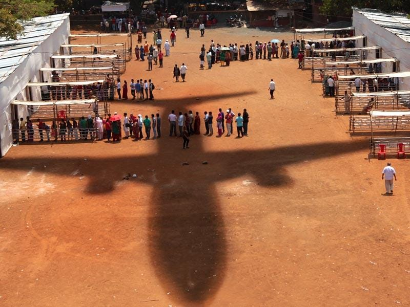 An aeroplane's shadow falls as voters queue up to cast their votes in the Lok Sabha elections in Mumbai. (Vijayanand Gupta/ HT photo)