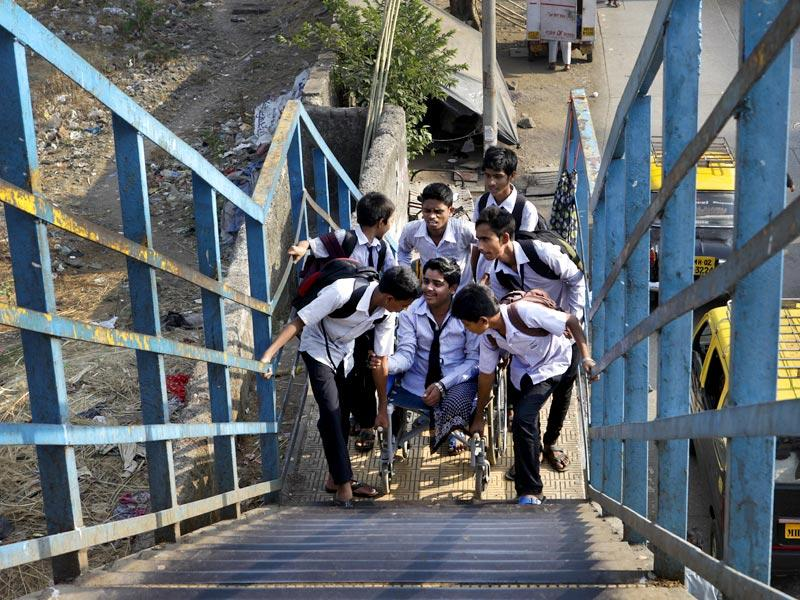 Firoz Khan, a 16-yr old student is helped by his classmates to travel from Mahim to Dharavi in Mumbai. Firoz had met with a train accident losing both his limbs at Dockyard Road Station on February 5, 2013 while returning home from school. (Kalpak Pathak/HT Photo)