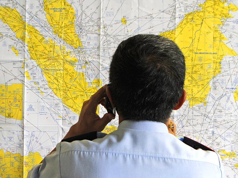 An airport official checks a map of Indonesia at the crisis center set up by local authority for the missing AirAsia flight QZ8501, at Juanda International Airport in Surabaya, East Java, Indonesia. (AP Photo)
