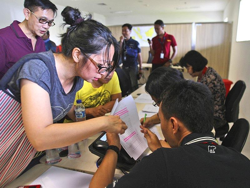 Relatives of the passengers onboard AirAsia flight QZ8501 check the plane's manifest at a crisis center set up by local authority at Juanda International Airport in Surabaya, East Java, Indonesia. (AP Photo)