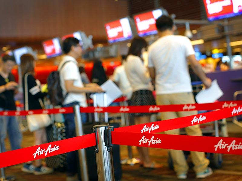 Passengers queue for their flights at the AirAsia check-in counter in Changi International Airport in Singapore. (AP Photo)