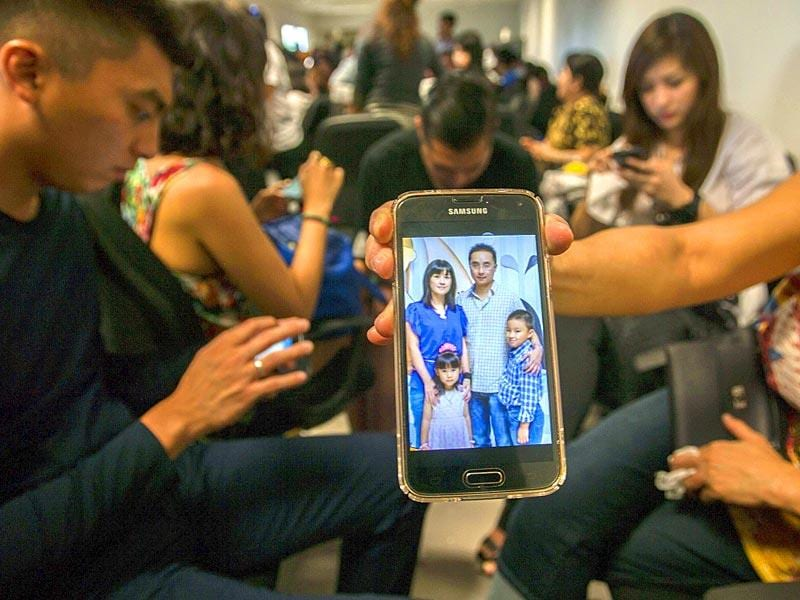 A relative shows a picture of alleged passengers who were travelling on missing Malaysian air carrier AirAsia flight QZ8501 on her mobile phone screen at the airport in Surabaya, East Java. (AFP Photo)