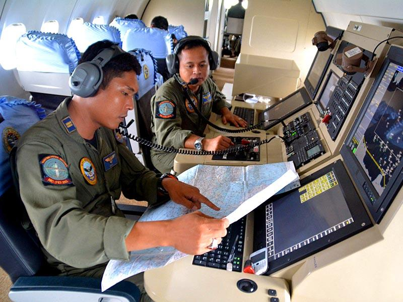 Two members from the Indonesian Navy's Tactical Commanding Operator (TACCO) help with the search for AirAsia flight QZ 8501on board a CN235 aircraft over Karimun Java in the Java Sea in this photo taken by Antara Foto (Reuters)