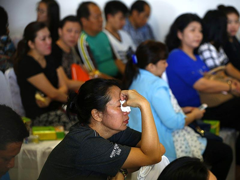 Family members of passengers onboard the missing AirAsia flight QZ8501 react as they await news in Juanda International Airport, Surabaya. (Reuters)