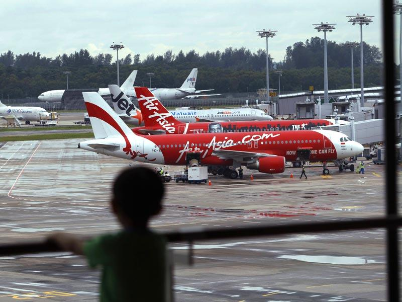 A child looks on at a viewing gallery overlooking AirAsia planes on the tarmac at Changi Airport in Singapore. (Reuters)