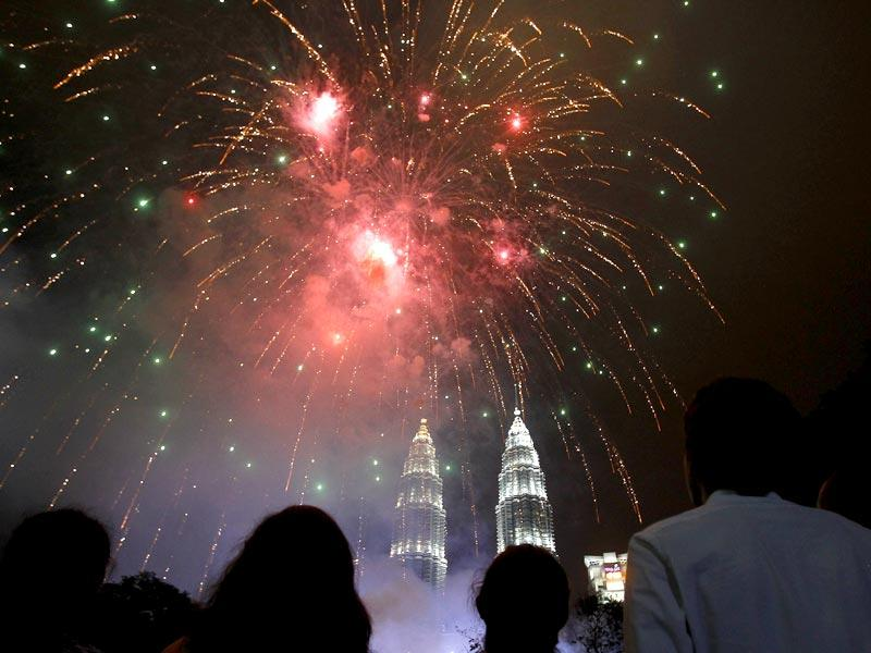 People watch fireworks explode over Malaysia's landmark Petronas Twin Towers during New Year celebrations in Kuala Lumpur. (AP Photo)