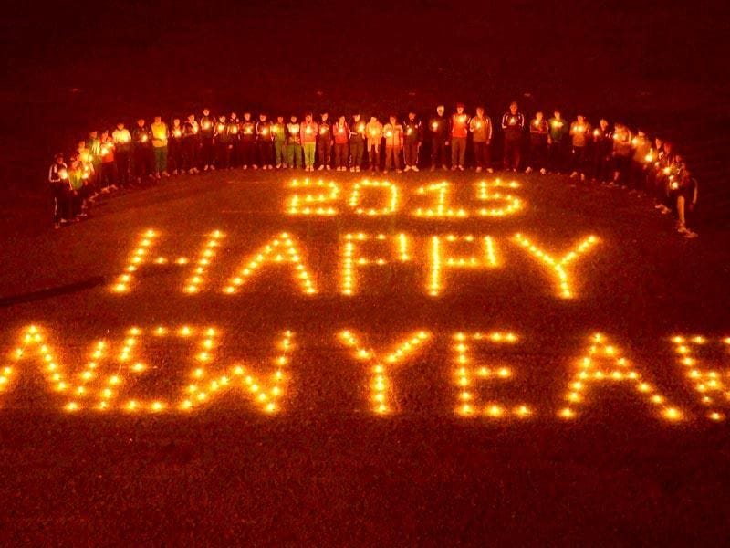 People light candles forming the words 'Happy new year 2015' on New Year's eve in Allahabad. (PTI Photo)