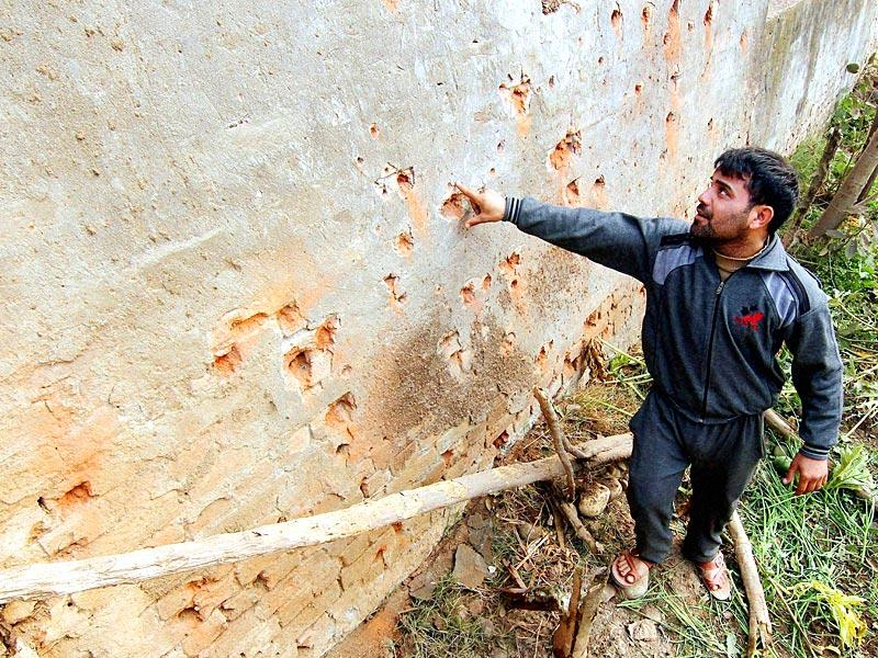 A villager shows mortar shell marks on the wall of his house after firing from the Pakistani side at Bainglad in Samba district. (PTI Photo)