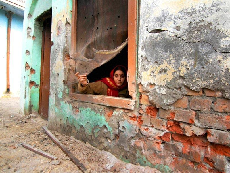 A woman sits by the window of a house damaged by shelling from the Pakistani side, at Bainglar village in Samba sector. (PTI Photo)
