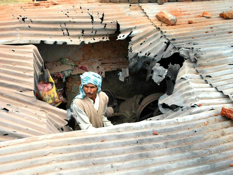 A villager inspects the roof of his house allegedly damaged in shelling from the Pakistani side, in the Samba sector. (Nitin Kanotra/HT Photo)