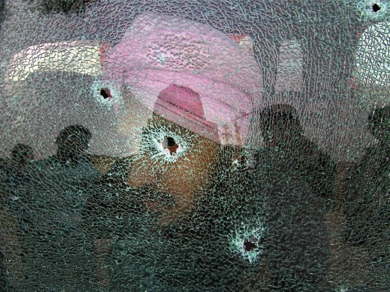 A villager shows the broken glass pane of his car after firing from the Pakistani side at Bainglad village in Samba district, some 58 kms from Jammu. (PTI Photo)