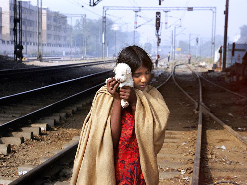 "Sanjana, 11, plays with a puppy on the railway tracks just beside her shanty near Okhla station in south Delhi. ""It is very hard to sleep in winter nights as we don't have enough warm clothes. I and my sisters hold each other tight at night when we feel too cold,"" said Sanjana. (Subrata Biswas/HT Photo)"