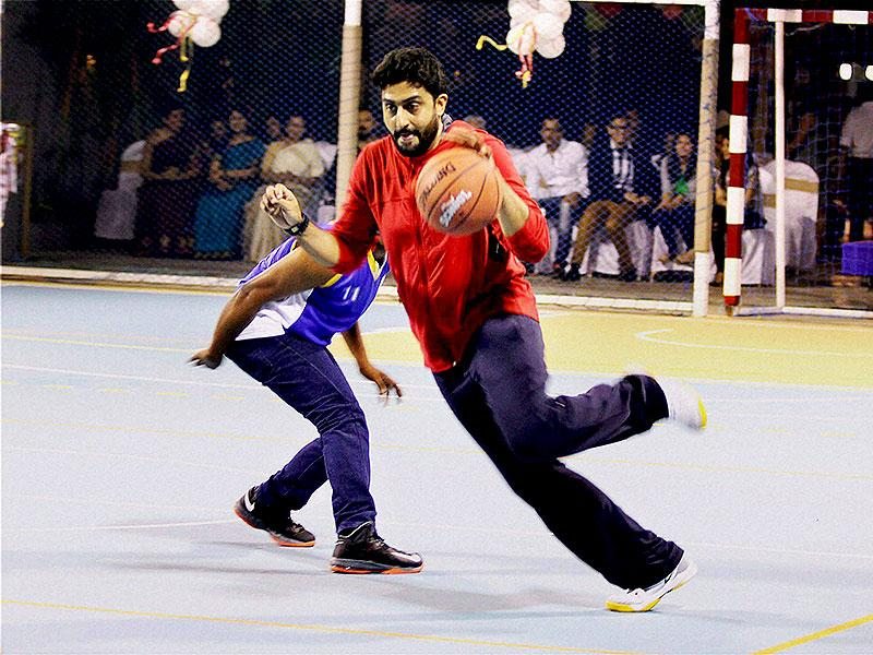 Bollywood actor Abhishek Bachchan plays basketball during the launch of a multi-sport court at Jamnabai Narsee School in Mumbai on Sunday. (PTI Photo)