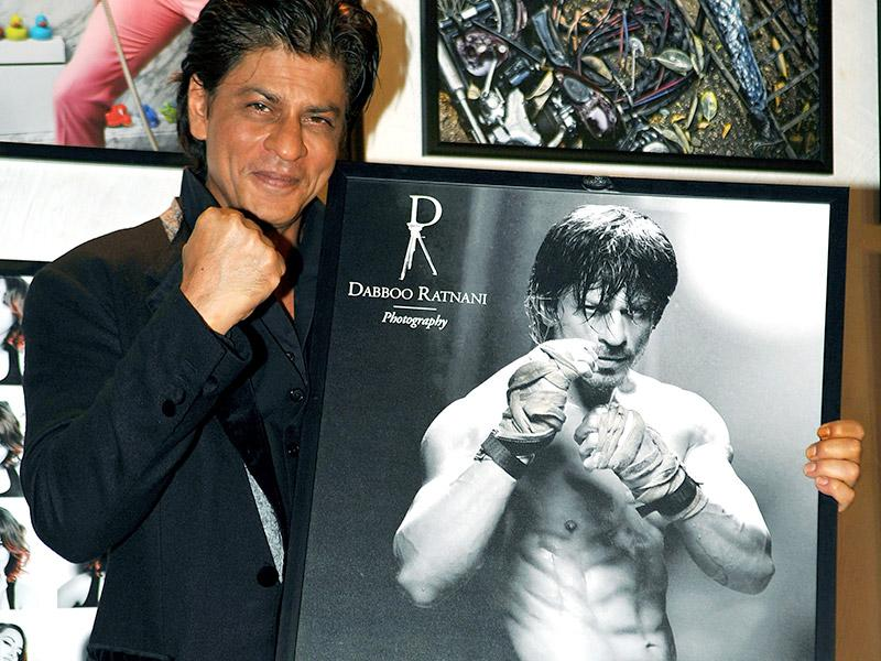 Shah Rukh Khan, who posed happily with his photo was seen flaunting his eight-pack abs; a similar pose to what he did during the making of Happy New Year for a promotional photograph that created a lot of buzz among fans.