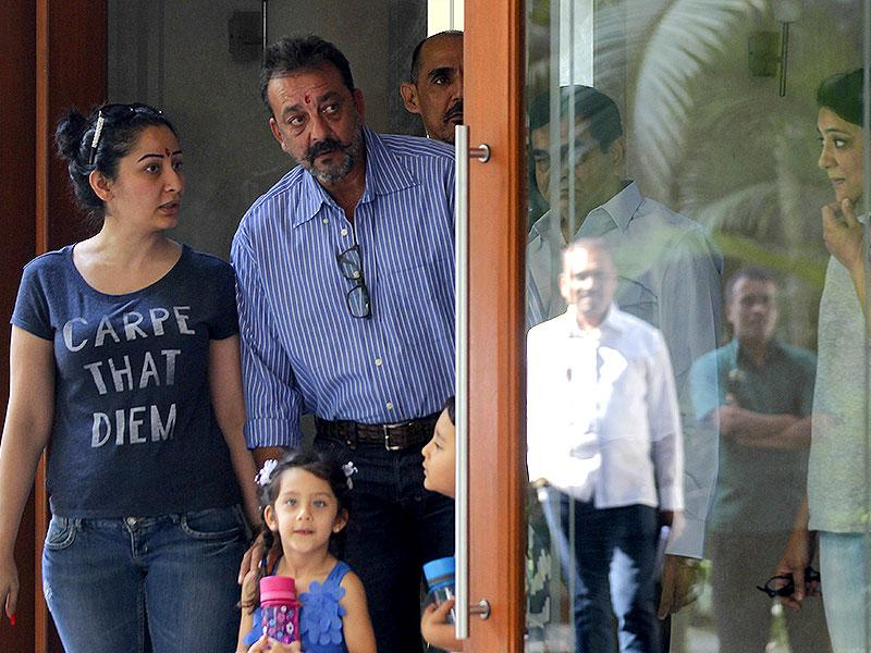 Sanjay Dutt with wife Manyata stand with kids even as sister Priya can be seen behind the glass door. Dutt left for Yerawada Jail after the end of his two weeks' furlough by the state prison authorities in Mumbai. (Photo by Vijayanand Gupta/ Hindustan Times)