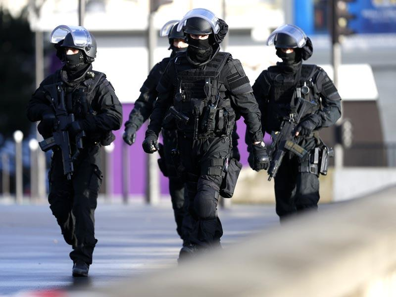 Members of the French police force walk above the