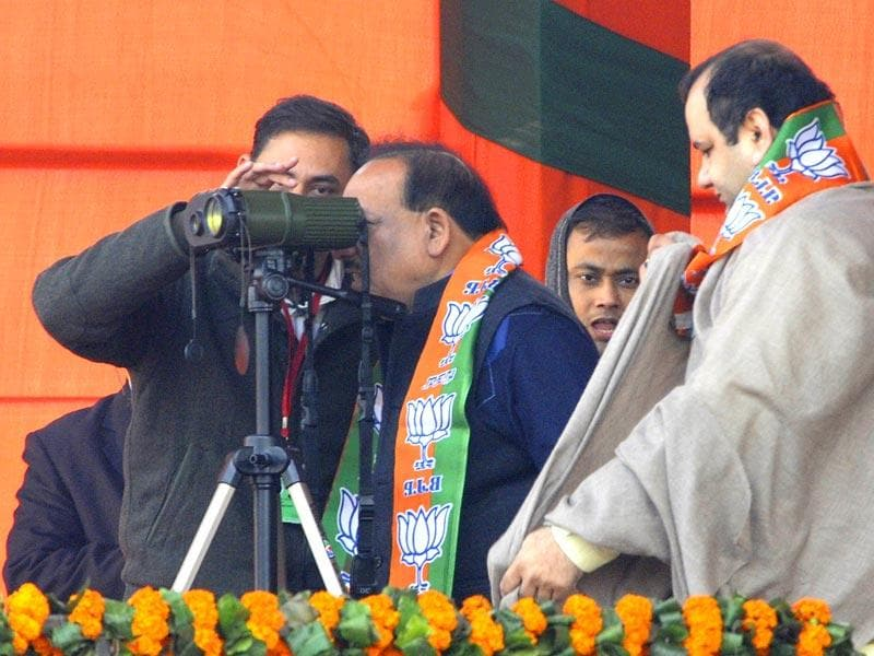 Union minister of Science and Technology Harsh Vardhan looks through the binoculars as Member of Parliament Mahesh Giri and Parvesh Verma wait for their turn during the BJP rally at Ramlila Maidan in New Delhi. (HT photo/Sonu Mehtal)