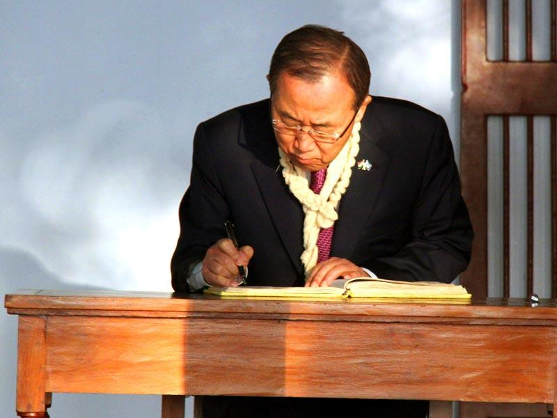 In this handout photograph released by Gujarat Information Bureau, UN Secretary General Ban Ki-moon writes in the visitor's book during his visit to the Gandhi Ashram in Ahmedabad . (AFP photo)