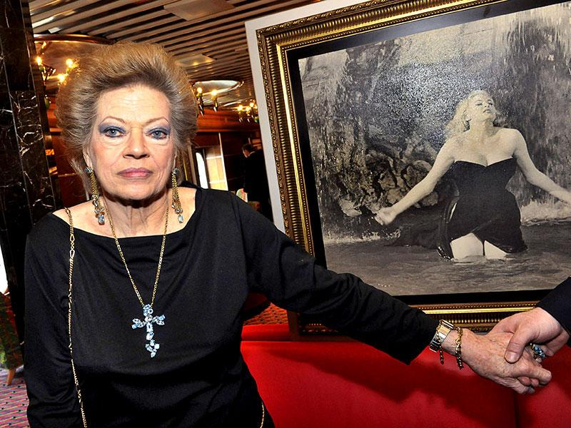 A picture taken on June 21, 2010 shows Swedish-born film star Anita Ekberg posing aboard the Italian cruise ship Costa Atlantica at quay in Stockholm next to a picture showing her famous swim in the Trevi fountain in La Dolce Vita by Italian director Federico Fellini in 1960. Anita Ekberg died near Rome, aged 83, media reports say on January 11, 2015. (AFP)