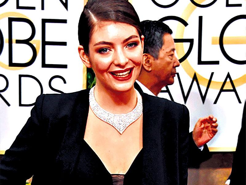 Suit up, ladies: Singer Lorde put up an androgynous appearance on the red carpet in a slouch suit. The slinky crop-top and red lips brought in the femme fatale punch to the outfit.