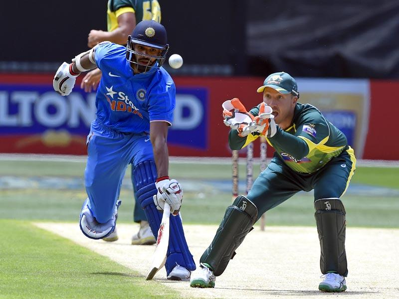 India's Shikhar Dhawan, left, avoids a run out as Australia's Brad Haddin, right, fields the ball during their one-day international cricket match in Melbourne, Australia . (AP photo)
