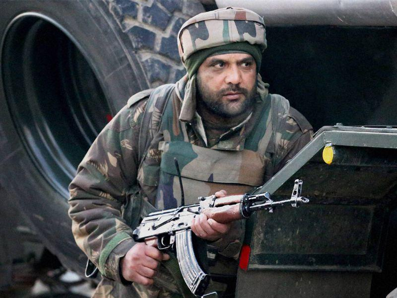 An army soldier takes position during an encounter that broke out between terrorists and security forces in North Kashmir's Sopore town on Sunday. PTI Photo