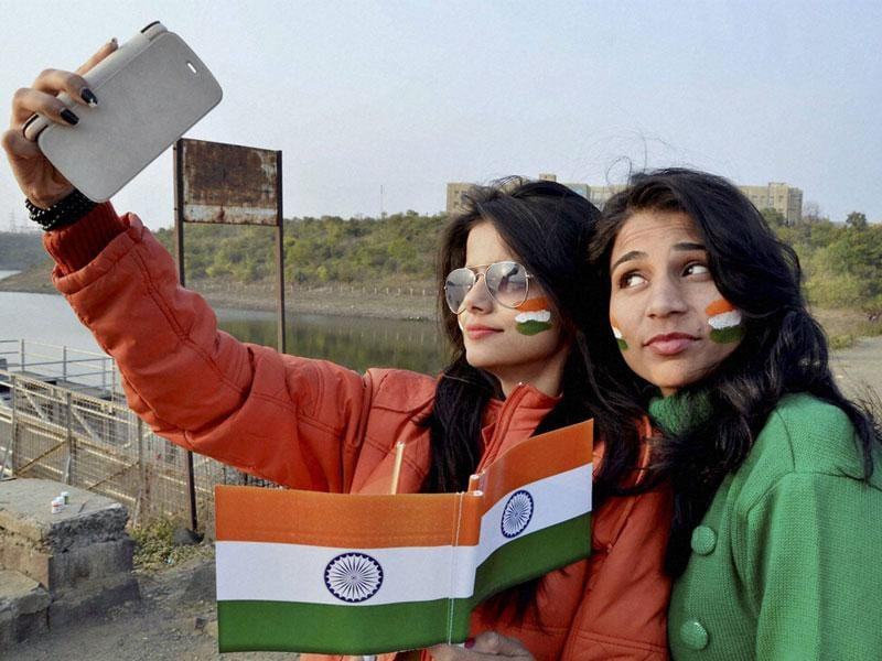 Young girls take a selfie with national flags as they gear up for Republic Day celebrations in Bhopal on Tuesday. (PTI photo)