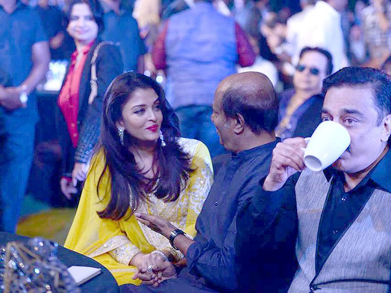 Aishwarya Rai Bachchan talks to Rajinikanth as Kamal Haasan watches the felicitation of Ilaiyaraaja was honoured at the music launch of Shamitabh, the movie that marks the music composer's 1000th venture. (Photo: ShamitabhTheMovie/Facebook)
