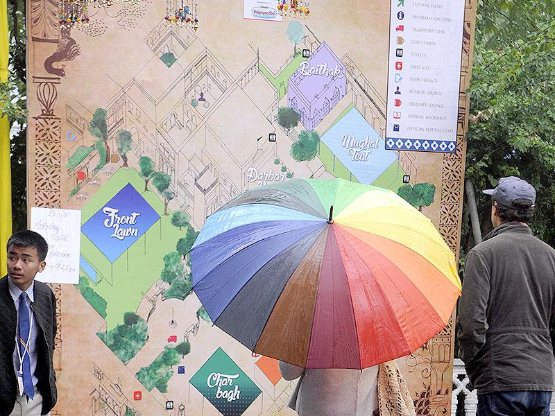 A visitor checks the map of venue on a cold day after many sessions got cancelled or changed due to overnight rains. Photo by - Himanshu Vyas/Hindustan Times