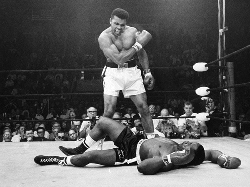 In this May 25, 1965, photo, Muhammad Ali stands over Sonny Liston shortly after dropping him less than two minutes into the first round of their heavyweight title fight, in Lewiston, Maine. Just months before the 50th anniversary of the fight, which remains one of the most controversial sporting events of the 20th century, both pairs of gloves are going on the auction block for the first time. (Text and Photo: AP)