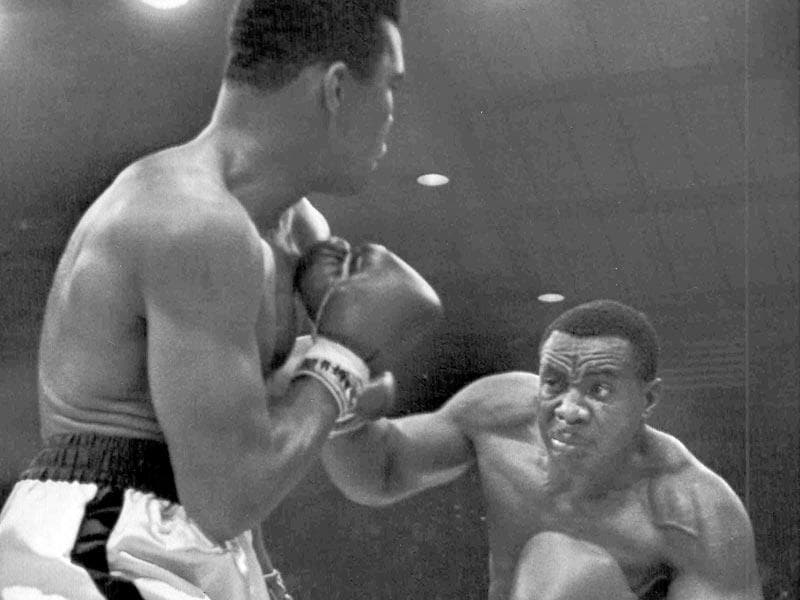 Sonny, right, lands a blow on Ali in the first moments of the fight. Given the controversial way the bout ended, the boxers' gloves were seized by George Russo, the boxing commissioner for Maine. The gloves remained in the Russo family until they were purchased several years ago by a California collector who is now selling them. (Text and Photo: AP)