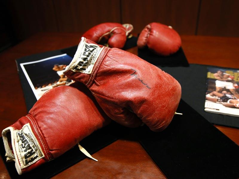 The gloves of Liston (front) and Ali (rear) sit on a table at Heritage Auctions by a photo and magazine depicting a moment captured during their 1965 fight. Ali signed both pairs of gloves when he came to Lewiston in 1995 to celebrate the fight's 30th anniversary. Liston died in 1970. (Text and Photo: AP)