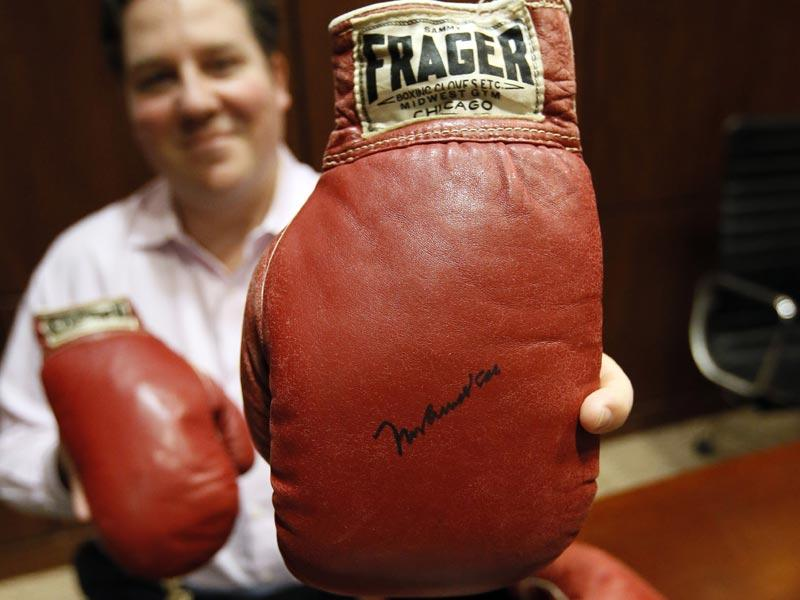 Chris Ivy, director of sports auctions at Heritage Auctions, holds the autographed gloves of Ali and Liston. There have been many theories about what exactly happened: Did Liston, an ex-con known as the Big Bear, throw the fight because he was in debt to the mob? Or did Ali actually deliver a perfectly landed punch? (Text and Photo: AP)