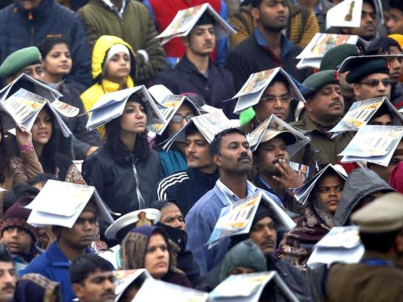Spectators cover themselves with brochure as it rains during Republic Day celebrations at Rajpath. (Ajay Aggarwal/HT Photo)