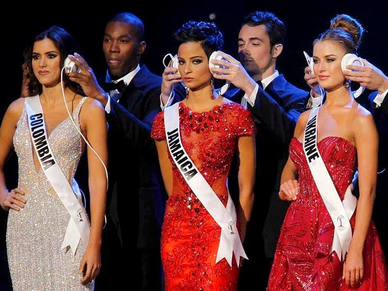 Miss Colombia Paulina Vega, the eventual winner, Miss Jamaica Kaci Fennell, and Miss Ukraine Diana Harkusha, who finished third, are seen with headphones during a question phase. (Reuters)